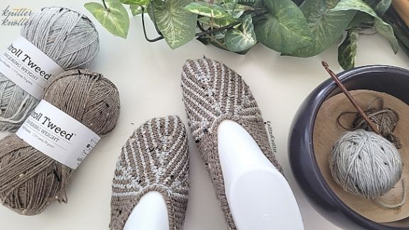 Tunisian crochet slippers in two colors - using short rows and Tunisian Simple Stitches. Picture contains a yarn bowl with left over yarn and a Tunisian Crochet Ginger Hook. It also shows the Stroll Tweed yarn that was used to make these slippers.