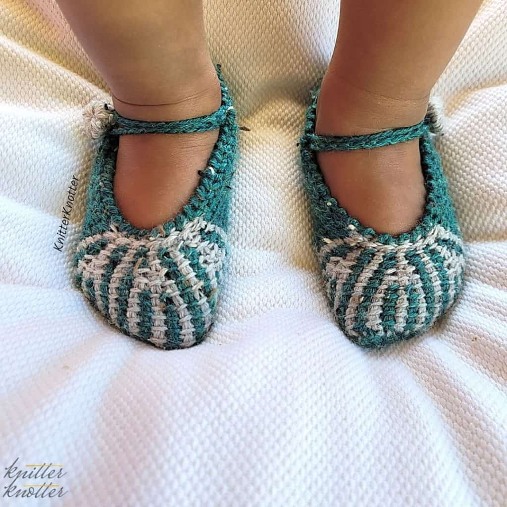 Baby version of the Ashvini Tunisian slippers - worn by a toddler. They look amazing on tiny feet and can be secured using a button and a chain.