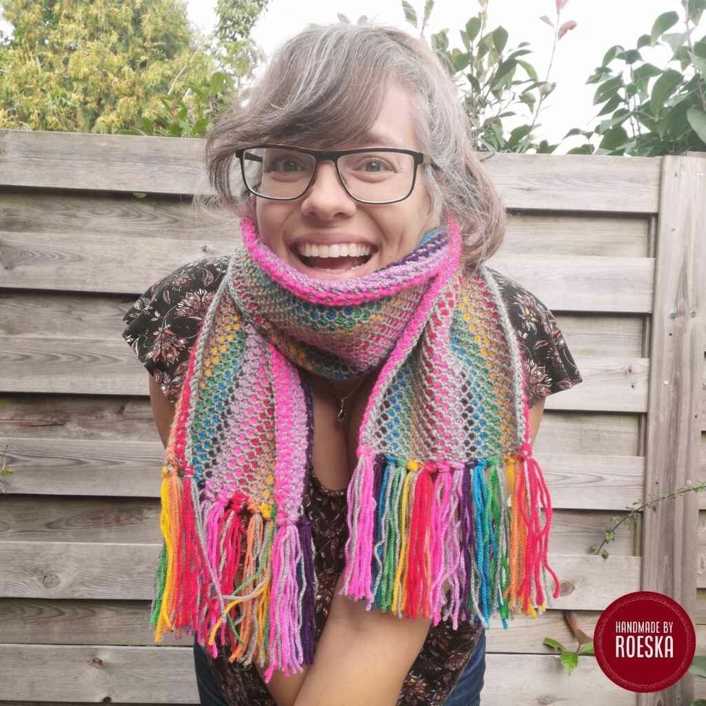 The Tunisian Rainbow Fringe Scarf is a colorful scarf designed by Roeska from Handmade by Roeska. In this pictures she is modeling her elegantly worn Tunisian crochet scarf made with Tunisian Simple and Purl stitches.